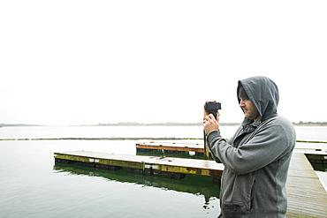 Side view of man photographing, Rockaway Beach, Oregon