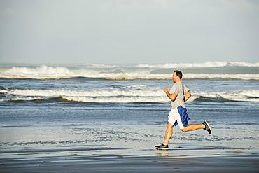 Mid adult man running on beach, Rockaway Beach, Oregon