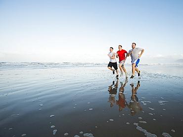 Men running on beach, Rockaway Beach, Oregon