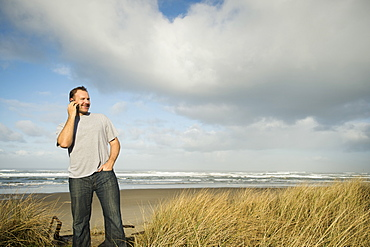 Man on phone while standing on beach, Rockaway Beach, Oregon