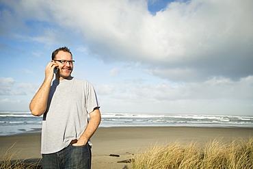 Mid adult man taking photograph, Rockaway Beach, Oregon