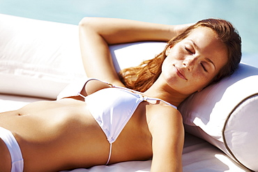 Young woman in bikini resting at swimming pool