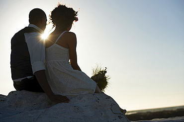 Newlywed couple looking at setting sun