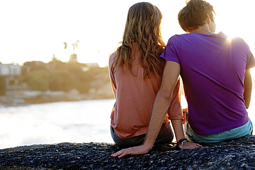Rear view of young couple sitting at beach