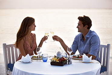 Couple eating at table on tropical beach, Thailand