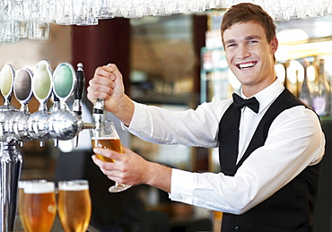 Portrait of bartender pouring beer