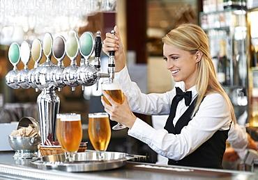 Female bartender pouring beer