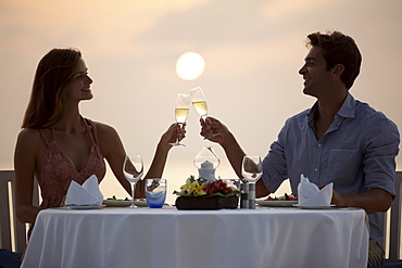 Couple at table on beach, toasting, Thailand