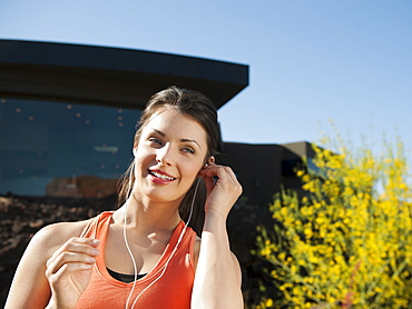 Young attractive woman plugging earphones in her ears, USA, Utah, St. George