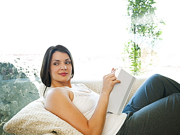 Young attractive woman reading book while sitting on sofa