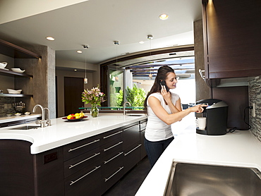Young woman making morning coffee while using mobile phone