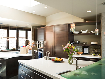 Young woman bustling around in modern domestic kitchen