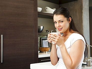 Young attractive woman enjoying her morning cup of coffee
