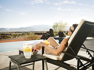 Young attractive woman enjoying cocktail by swimming pool, USA, Utah, St. George