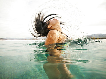 Attractive young woman emerging from swimming pool, USA, Utah, St. George