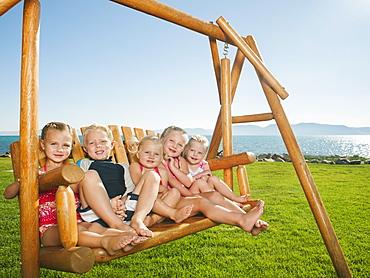 Portrait of children (2-3, 4-5) on swing, USA, Utah, Garden City
