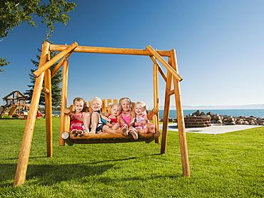 Portrait of children (2-3, 4-5) swinging, USA, Utah, Garden City