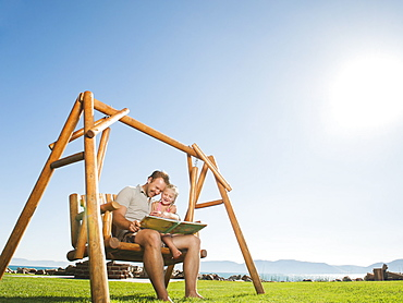 Father with daughter (4-5) on swing reading book, USA, Utah, Garden City