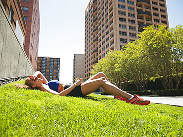 USA, California, Los Angeles, Young woman listening to music while lying on grass after training, USA, California, Los Angeles