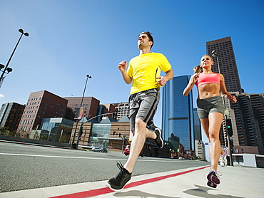 USA, California, Los Angeles, Young man and young woman running on city street, USA, California, Los Angeles