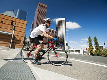 USA, California, Los Angeles, Young man road cycling on city street, USA, California, Los Angeles