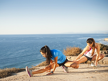 USA, California, San Diego, Two women stretching at sea coast