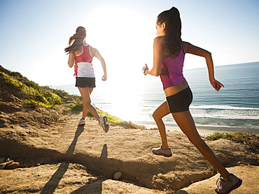 USA, California, San Diego, Two women jogging along sea coast