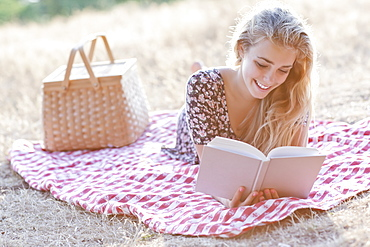 Happy teenage girl (16-17) reading book outdoors