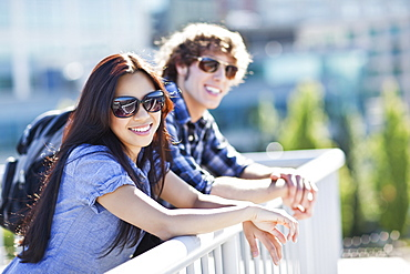 Couple standing by banister outdoors