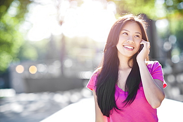 Young chinese woman using mobile phone outdoors