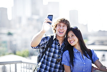 USA, Washington, Seattle, Couple wearing sunglasses photographing themselves with smart phone