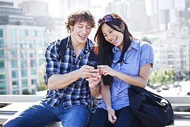USA, Washington, Seattle, Couple looking at mobile phone