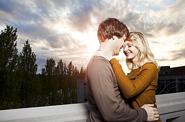 Young couple embracing under sunset sky