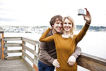 USA, Washington, Seattle, Young couple taking photos on pier