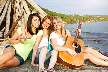 Portrait of three young women hanging out on beach