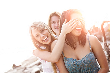 Three young women hanging out, covering eyes and laughing