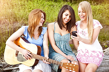 Three young women with guitar and cell phone relaxing