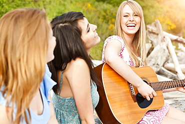 Young women playing guitar on beach