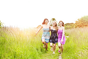 Three young women running in meadow