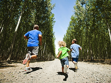 Father with sons (2-9) running up country road