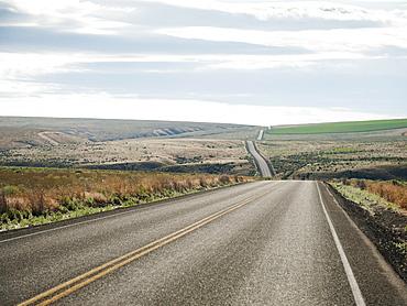 USA, Oregon, Boardman, Rolling landscape with empty road