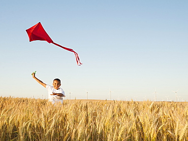 Boy (10-11) playing with kite in wheat field