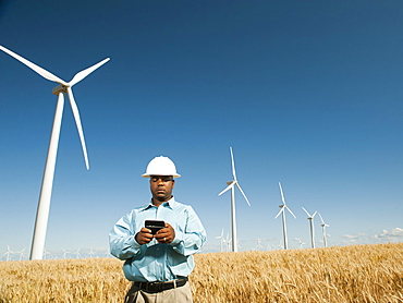 USA, Oregon, Wasco, Engineer standing in wheat field in front of wind turbines, using mobile phone