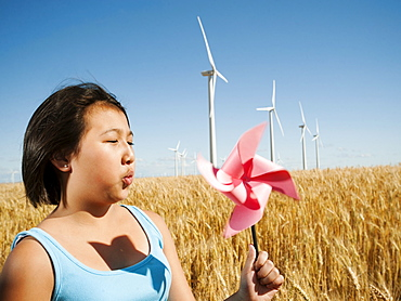 USA, Oregon, Wasco, Girl (10-11) holding blowing at fan in wheat field with wind turbines in background