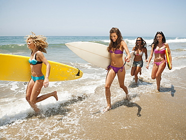 Group of young attractive women running into water with surfboards