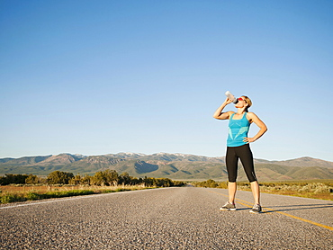 Mid adult woman drinking water while taking break from running on empty road
