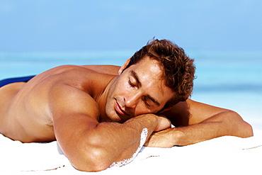 Handsome man taking sunbath at the beach