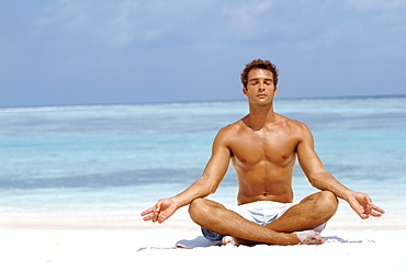 Handsome young man meditating in a lotus position on the beach