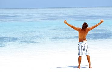 Man standing with his arms wide open on beach