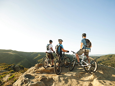 USA, California, Laguna Beach, Two bikers on hill looking at view